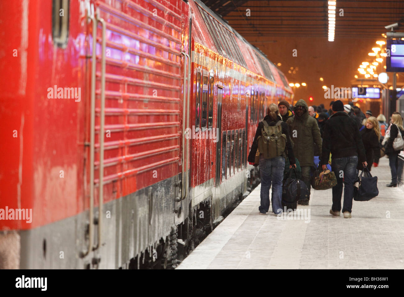 travelers boarding an icy train, winter conditions on the roofed station platforms - Stock Image