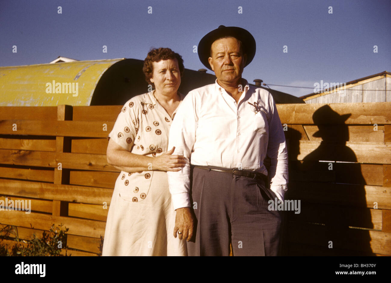 Old married couple standing by a fence in the American West during the 1950s or 1960s. - Stock Image