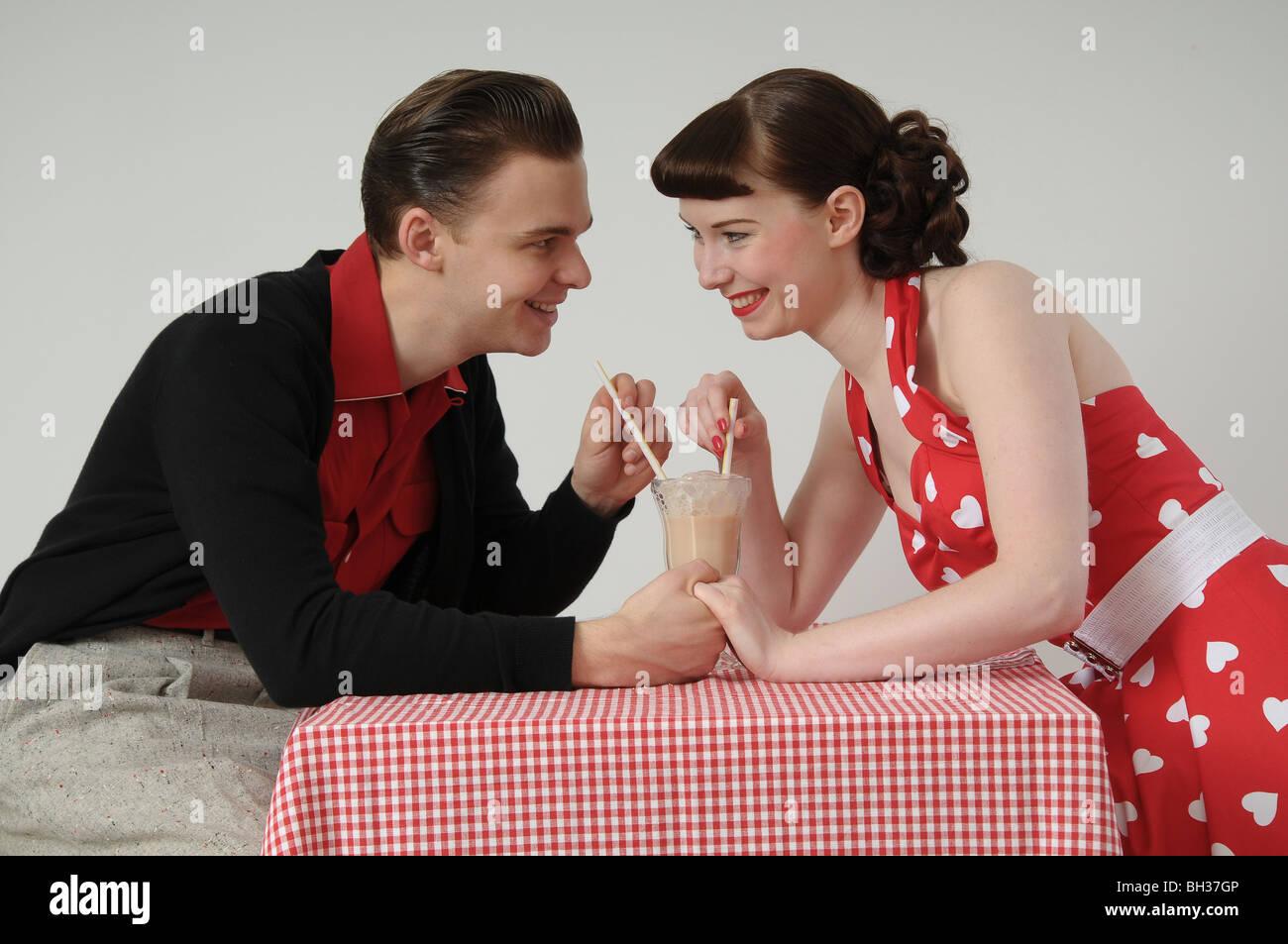 Couple sharing a milkshake in 1950s diner - Stock Image