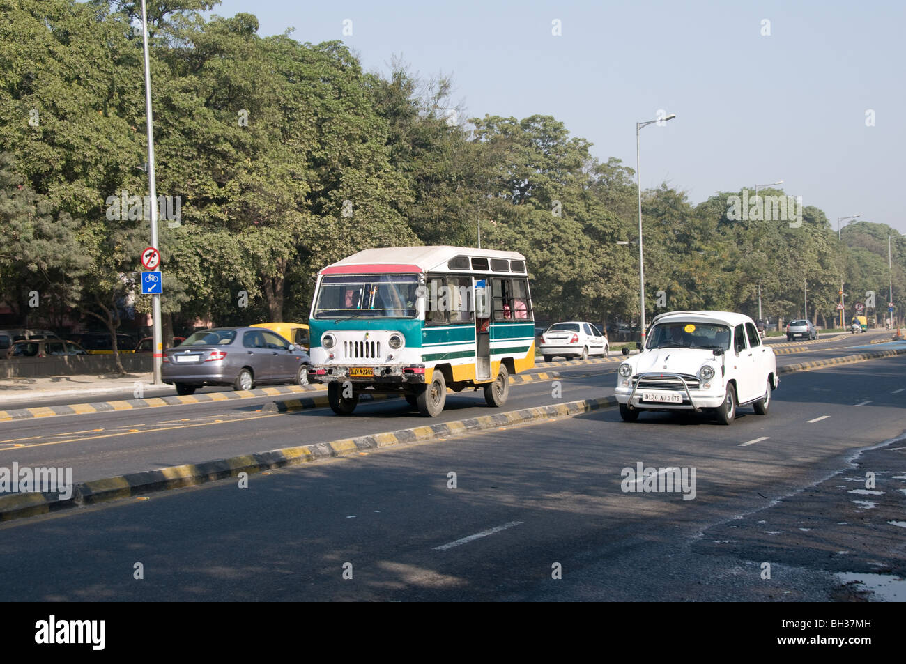 An India minibus drives down the Delhi BRT priority bus lane while there is an Ambassador car on the normal road - Stock Image