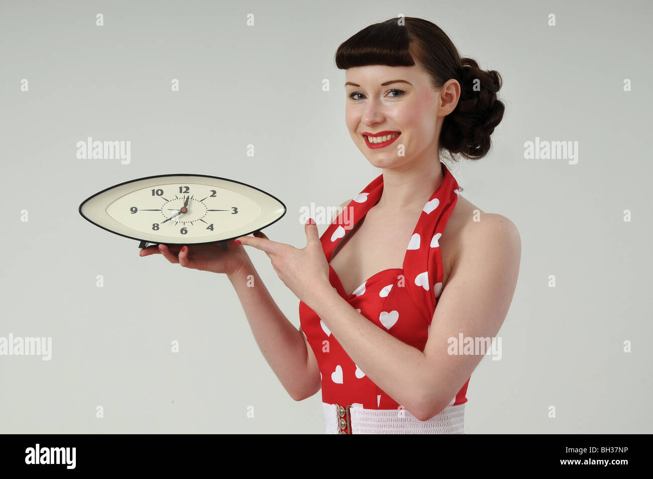 Pretty girl in 1950s style dress holding a clock - Stock Image