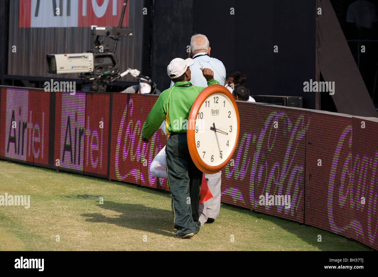 An Indian man carries a large clock around the outfield of the Kotla Stadium in New Delhi, India. Picture by James - Stock Image
