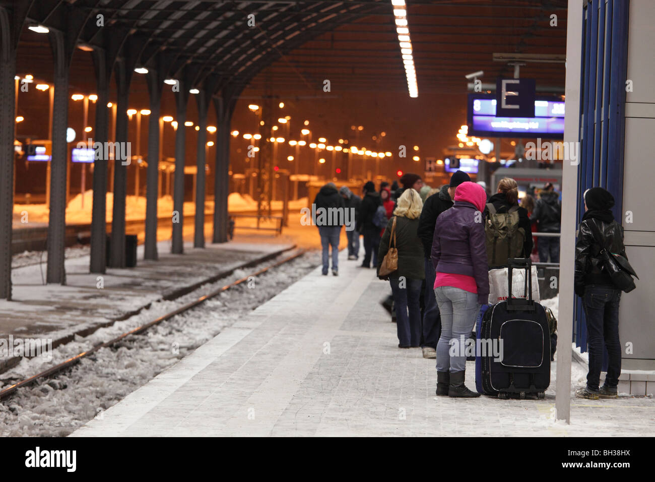 travelers on train platform waiting in winter for the delayed train - Stock Image