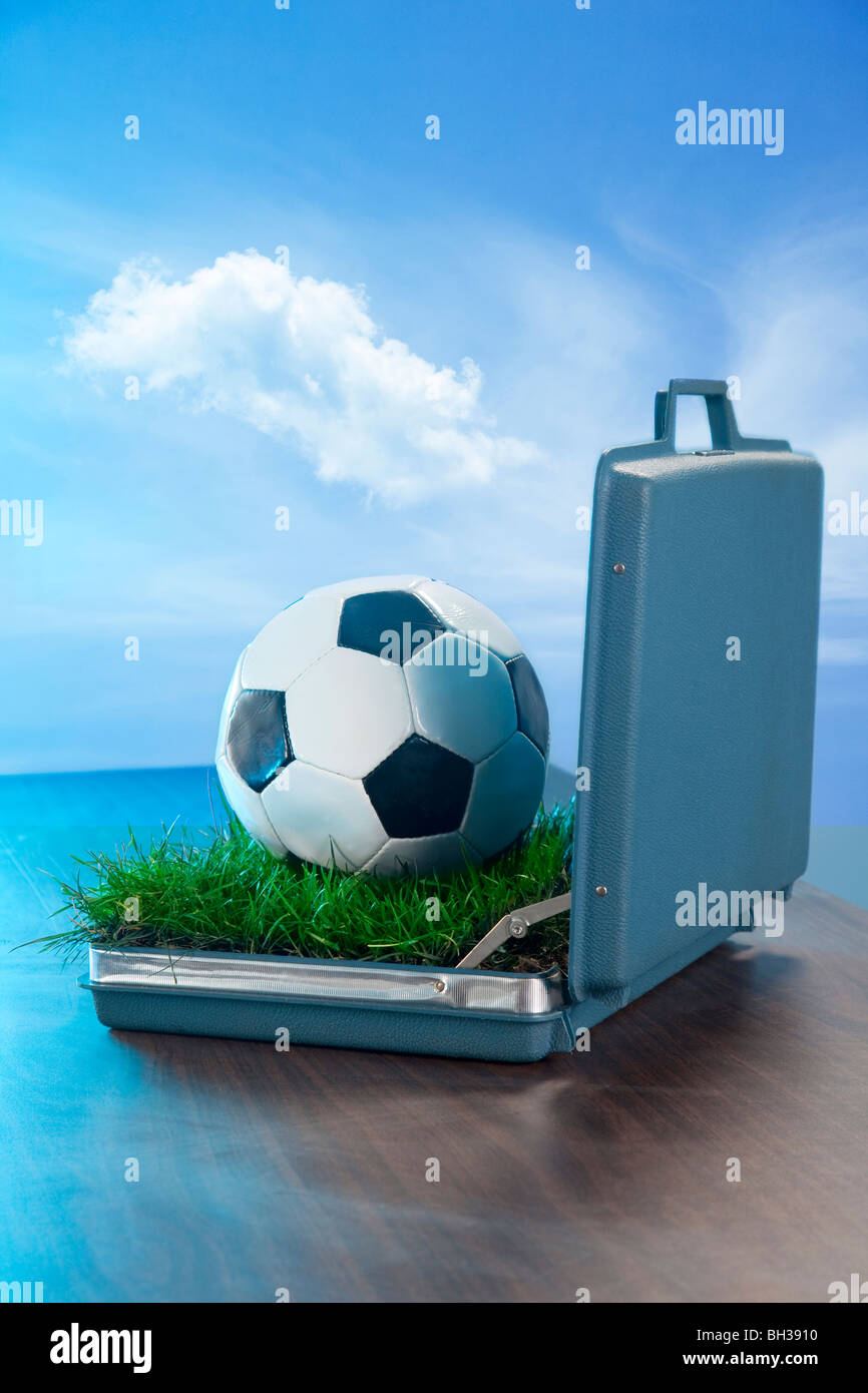 open briefcase on desk with soccer ball and grass inside - Stock Image