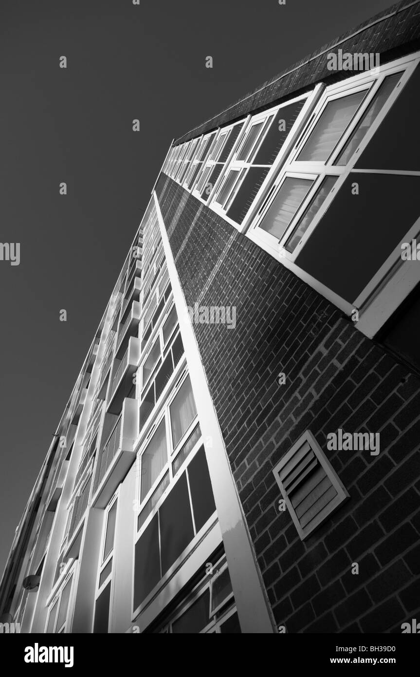 Monotone view of  a British city Council estate block of flats on a cold sunny day looking upward towards the sky. - Stock Image