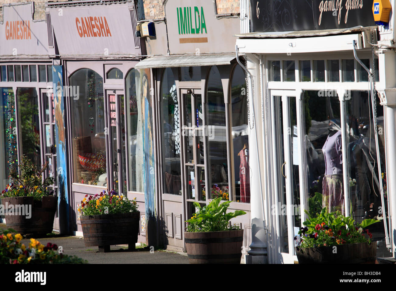 A parade of old but trendy shop fronts with flower containers outside and colourful fascias. Window displays partially - Stock Image