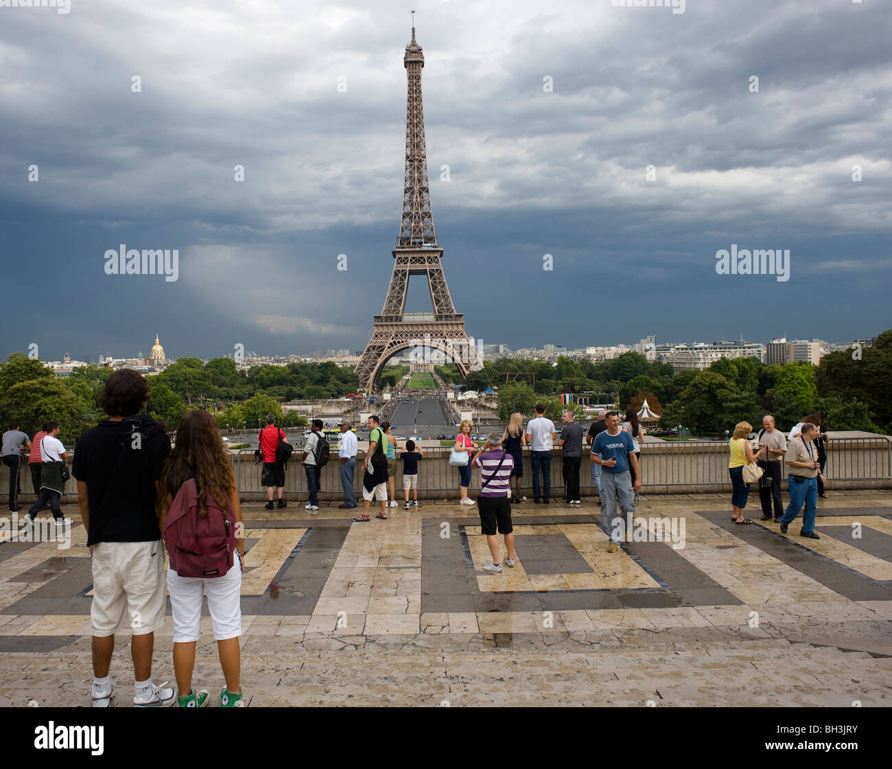 A storm clears as tourists take pictures on the Palais de Chaillot looking towards the Eifel Tower, Paris, France, - Stock Image
