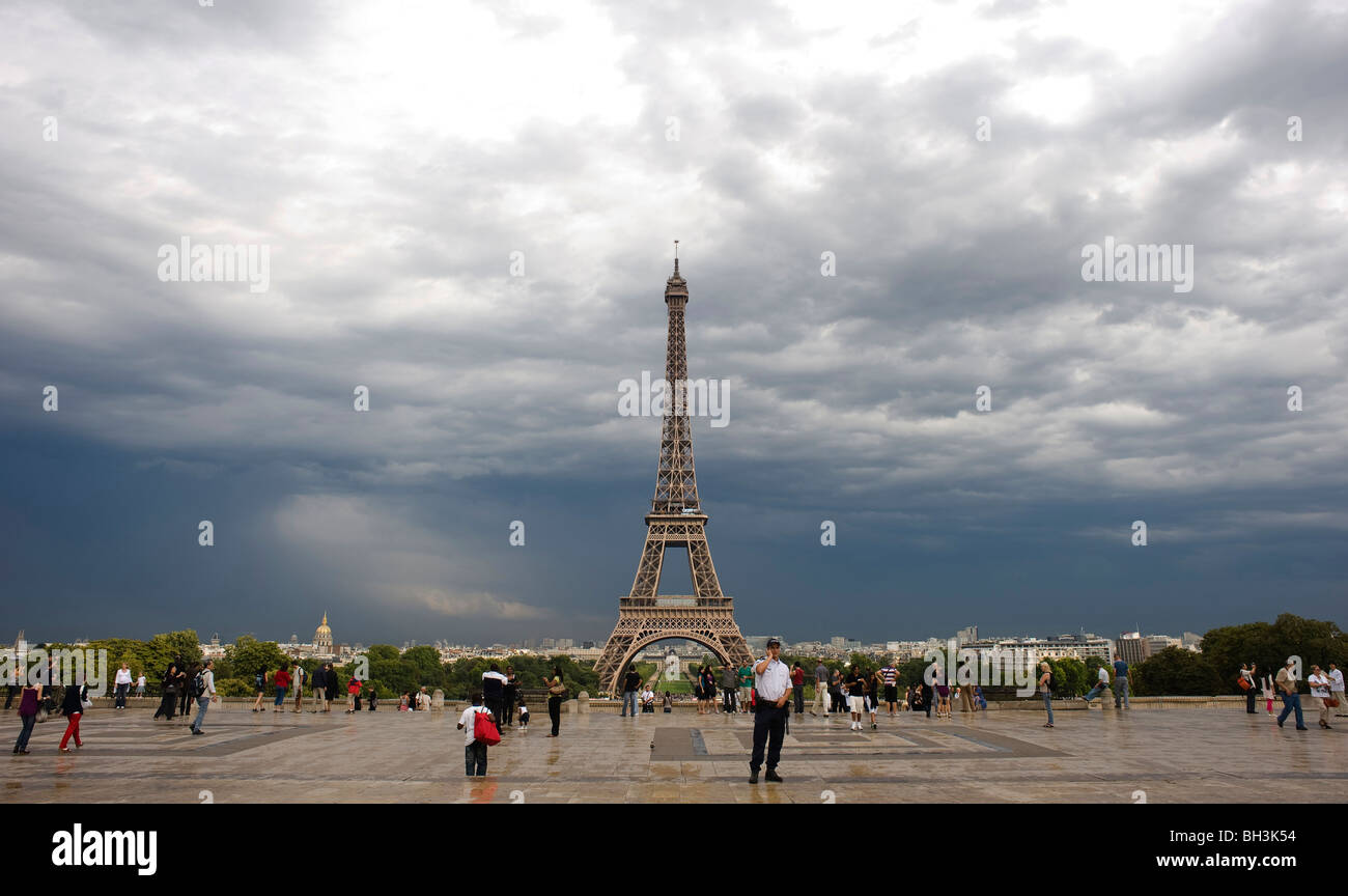 A storm clears as tourists take pictures, the Gendarmarie talks on the phone, on the Palais de Chaillot - Stock Image