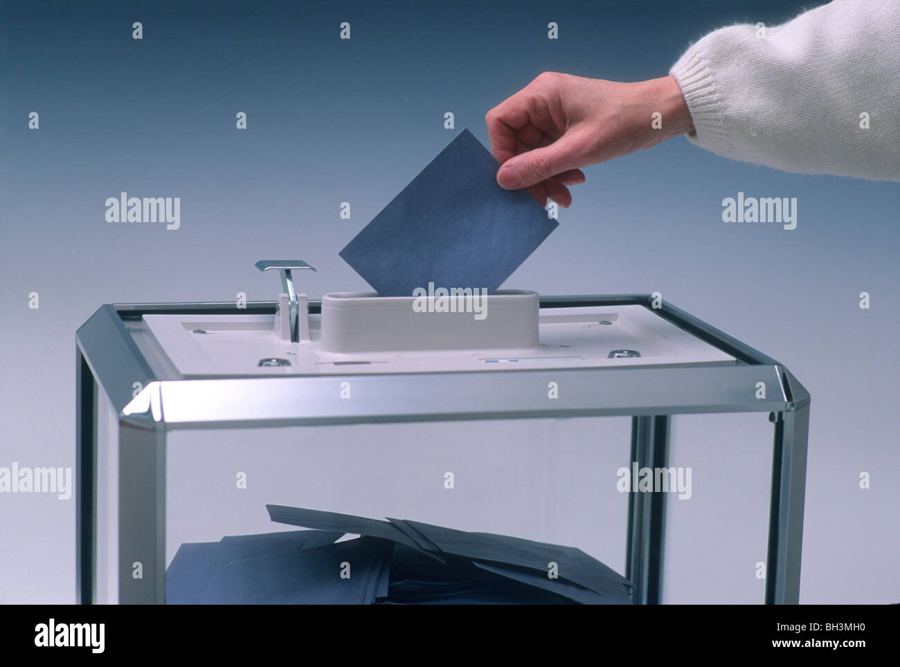 Hand putting a vote into a ballot box. - Stock Image