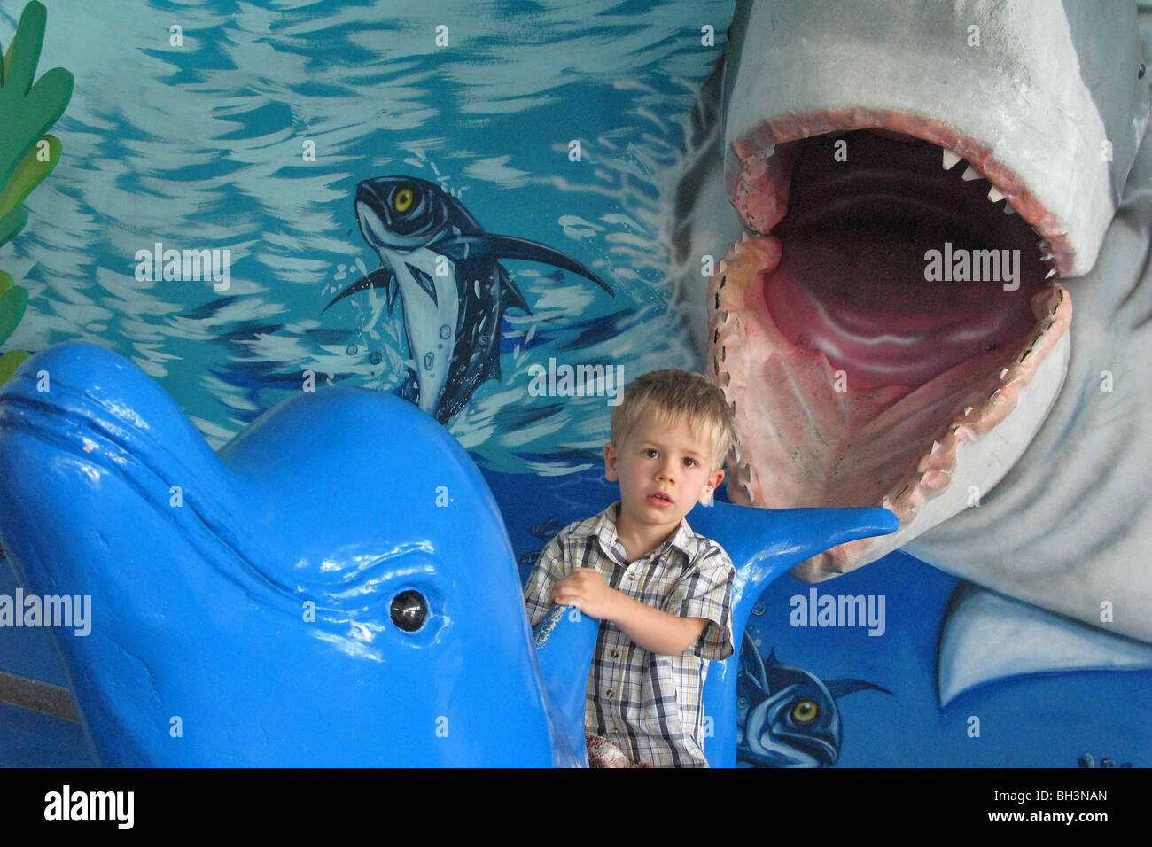 CHILD SITTING ON A DOLPHIN WITH A PAINTING OF AN OPEN-MOUTHED SHARK, PRACHUAP KHIRI KHAN AQUARIUM, THAILAND - Stock Image