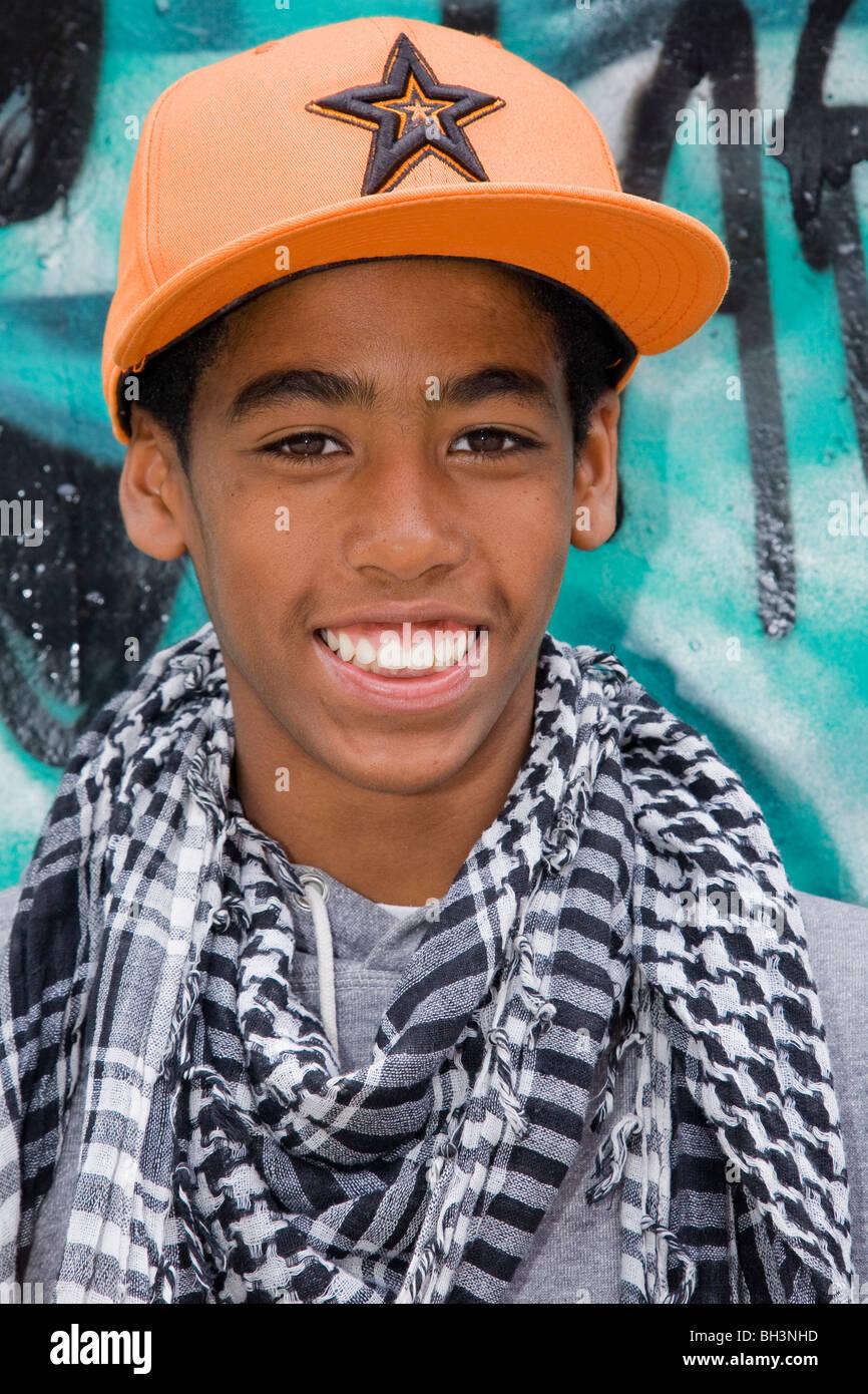 Black Teenager against graffiti wall - Stock Image