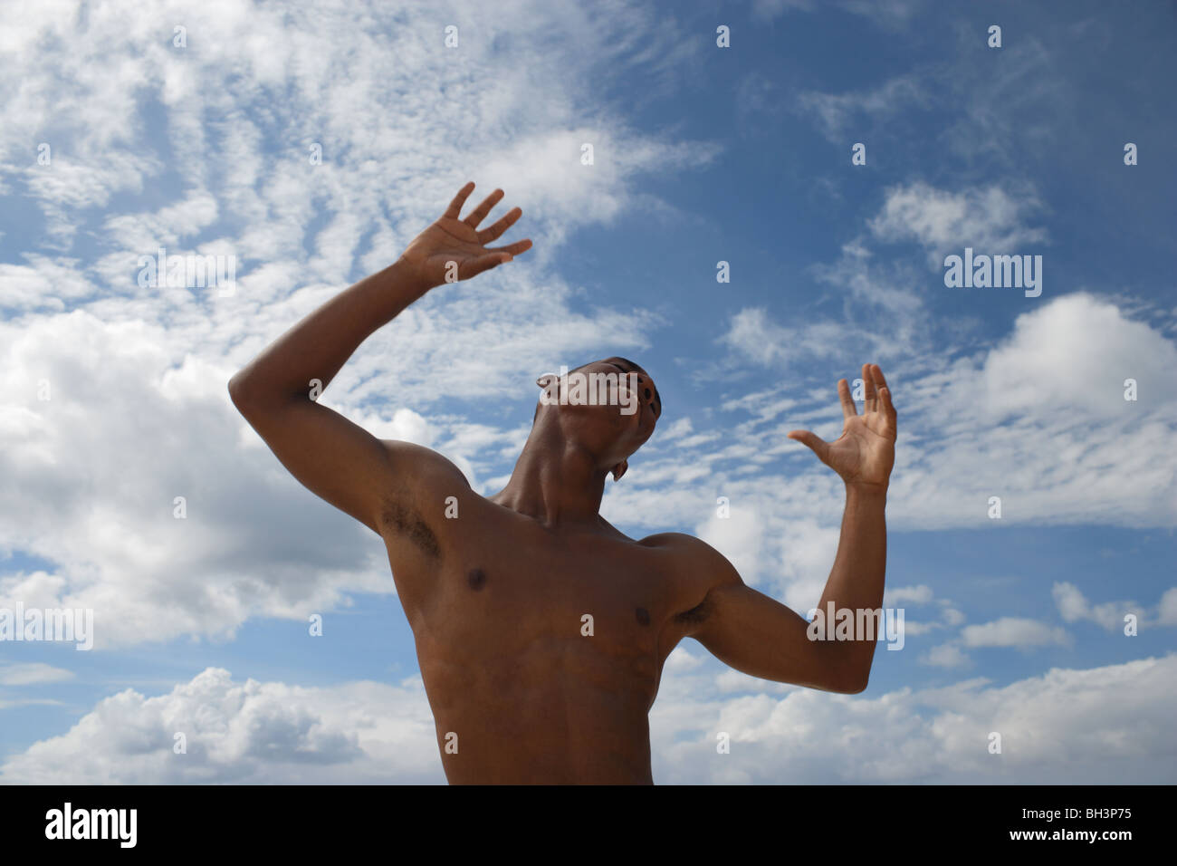 Young man dancing against a blue cloudy sky, smiling - Stock Image