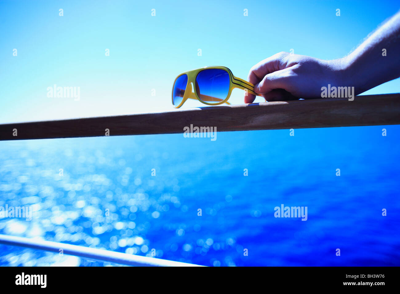 A man's hand holding on to a pair of retro yellow sunglasses resting on a wooden handrail on a cruise ship against - Stock Image