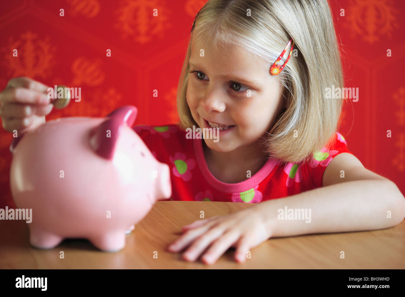 Young girl putting money into a pink piggy bank, smiling - Stock Image