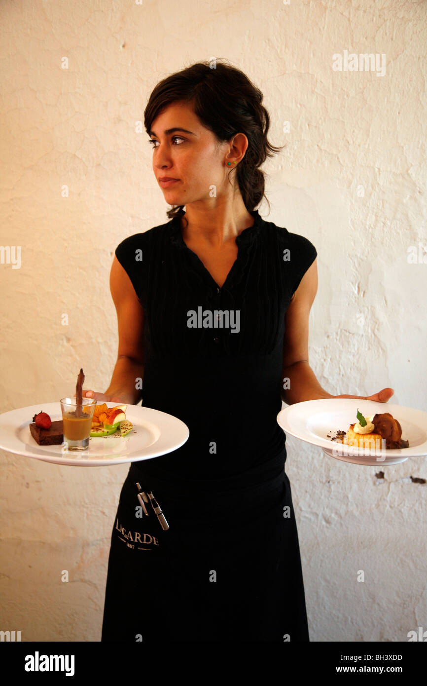 Waiter at the upmarket restaurant of Lagarde winery holding two plates of deserts, Lujan de Cuyo, Mendoza, Argentina. - Stock Image