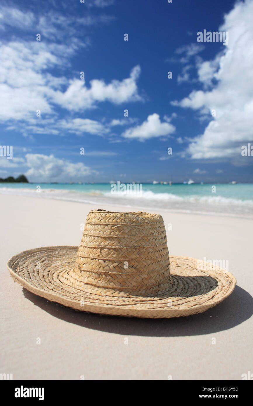 A straw hat lying on the sand on a deserted tropical beach - Stock Image