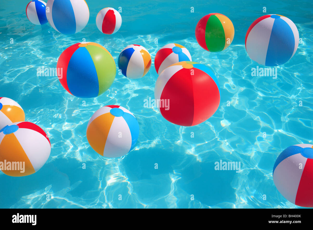 Brightly colored inflatable beach balls randomly floating in a blue water swimming pool - Stock Image