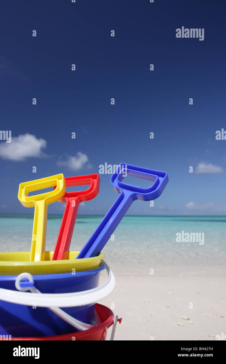 Three children's toy buckets and spades on a deserted tropical beach - Stock Image