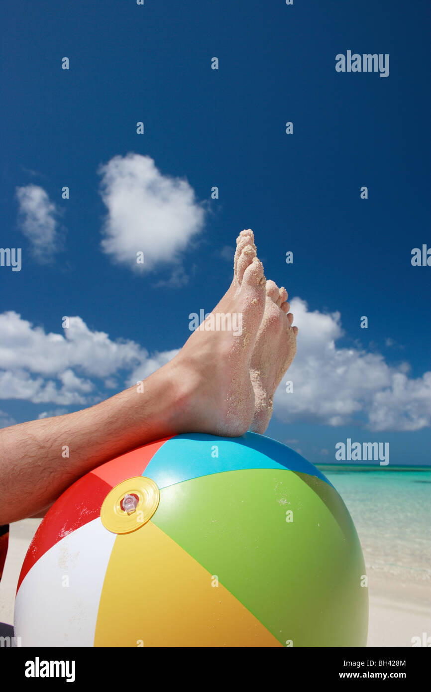 A man's legs and feet resting on an inflatable multi colored beach ball on a tropical beach - Stock Image