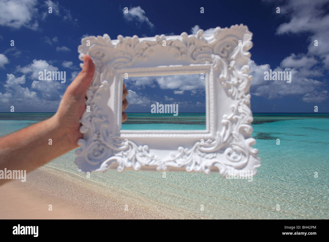 A man's hand holding a white ornate picture frame in the air against a deserted tropical beach - Stock Image