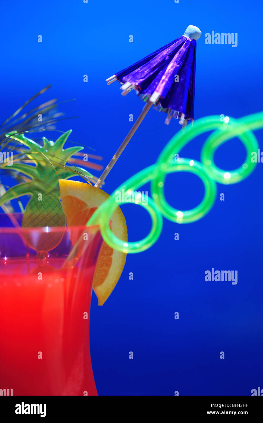 A close up of a tropical cocktail against a blue summer sea and sky - Stock Image