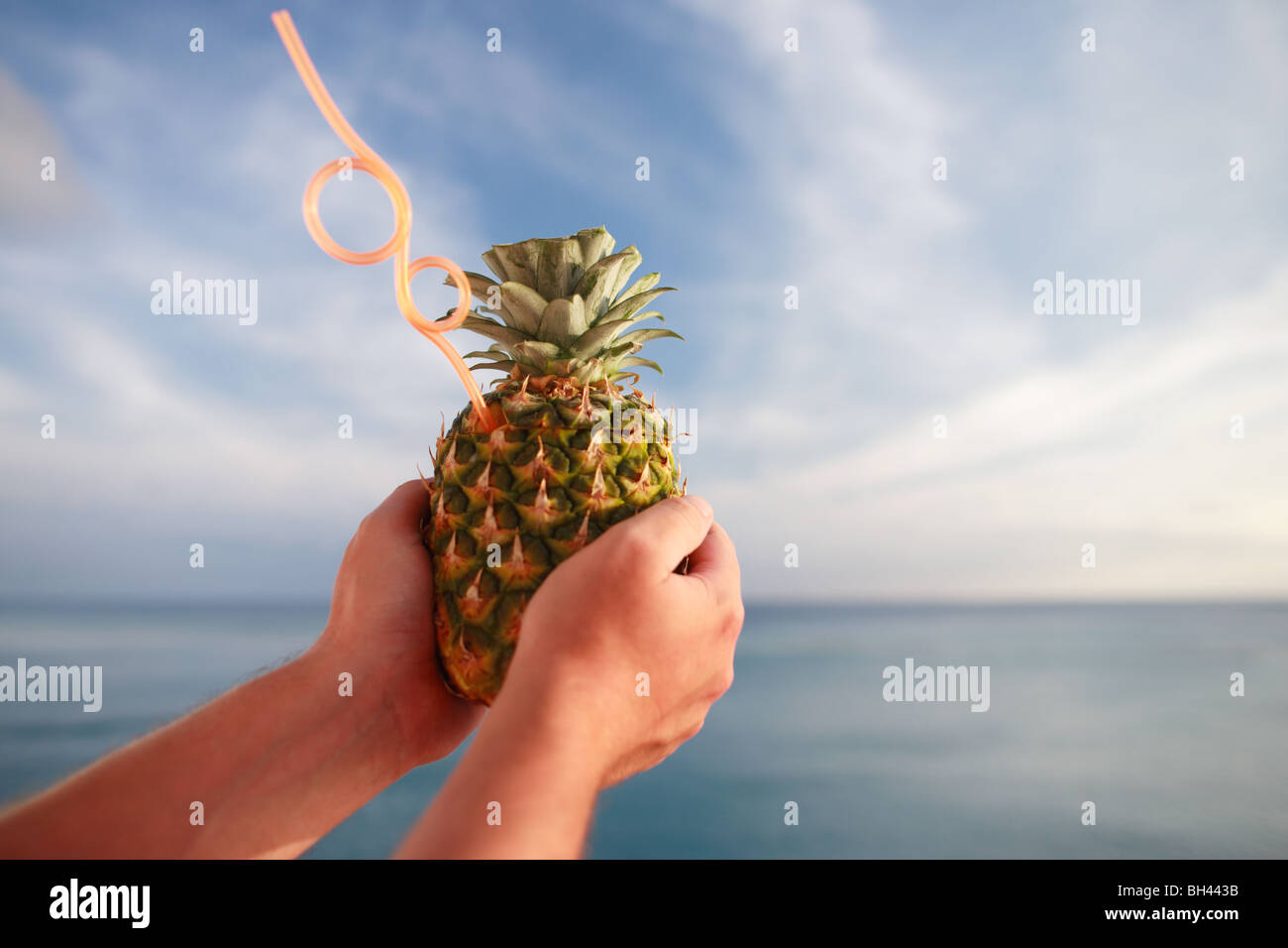 A man's hands holding a tropical pineapple cocktail drink with a straw against a blue sea and sky - Stock Image