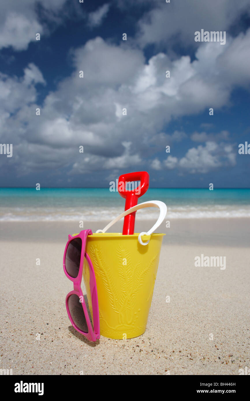 A yellow bucket, spade and a pair of sunglasses on a deserted tropical beach - Stock Image