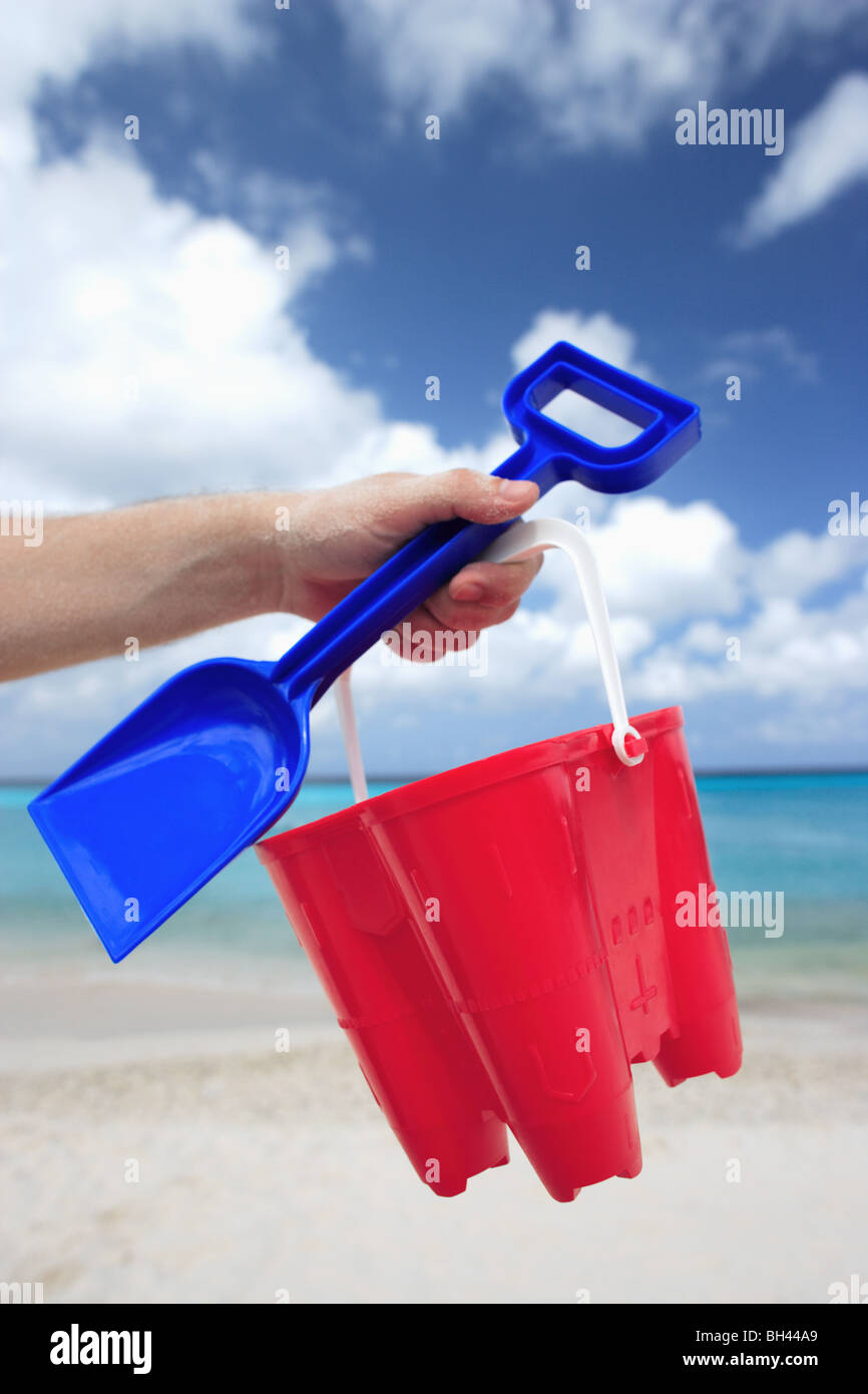 A man's hand holding a toy bucket and spade in the air on a deserted tropical beach - Stock Image