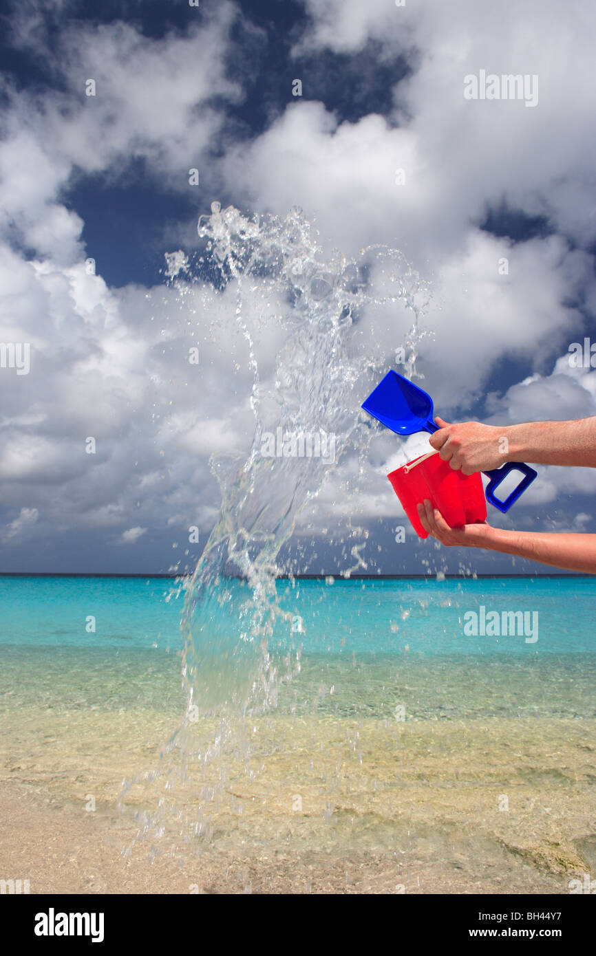 A man's hands throwing a child's toy bucket and spade full of water in the air on a deserted tropical beach - Stock Image
