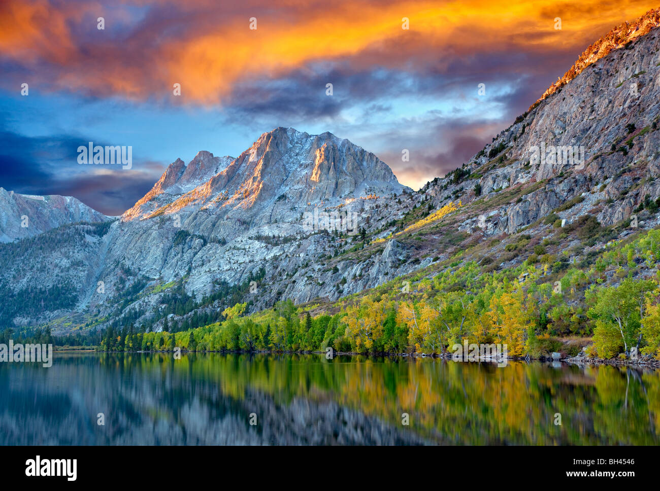 Silver Lake reflection with fall colored cottonwood trees and sunrise. California. Sky has been added. - Stock Image
