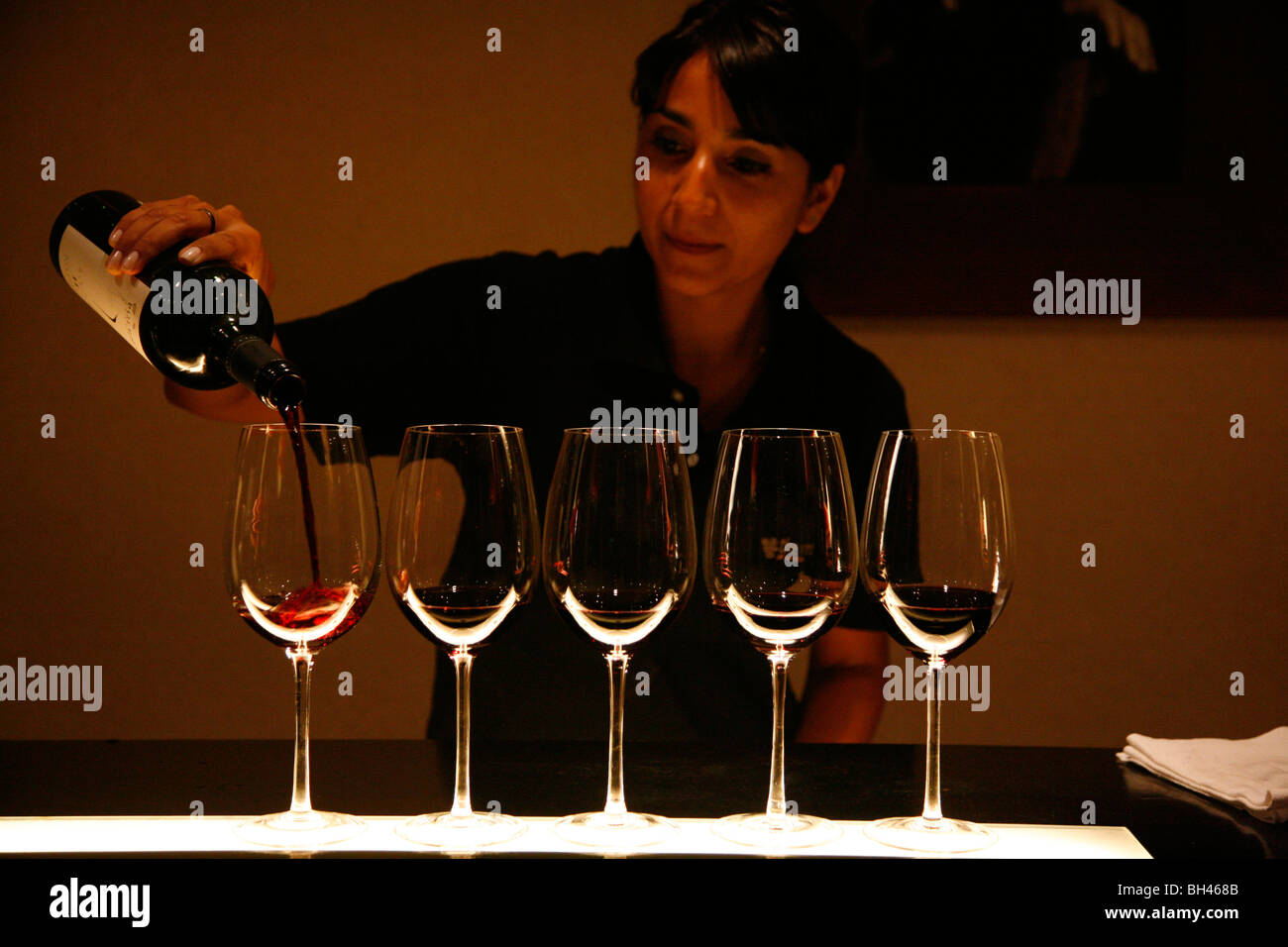Woman pouring wine at the tasting room of Vines of Mendoza wine bar, Mendoza, Argentina. - Stock Image