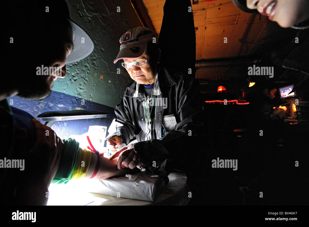 A customer undertakes a AIDS test offered free-of-charge by a doctor of an HIV awareness group at a bar in Tokyo, - Stock Image