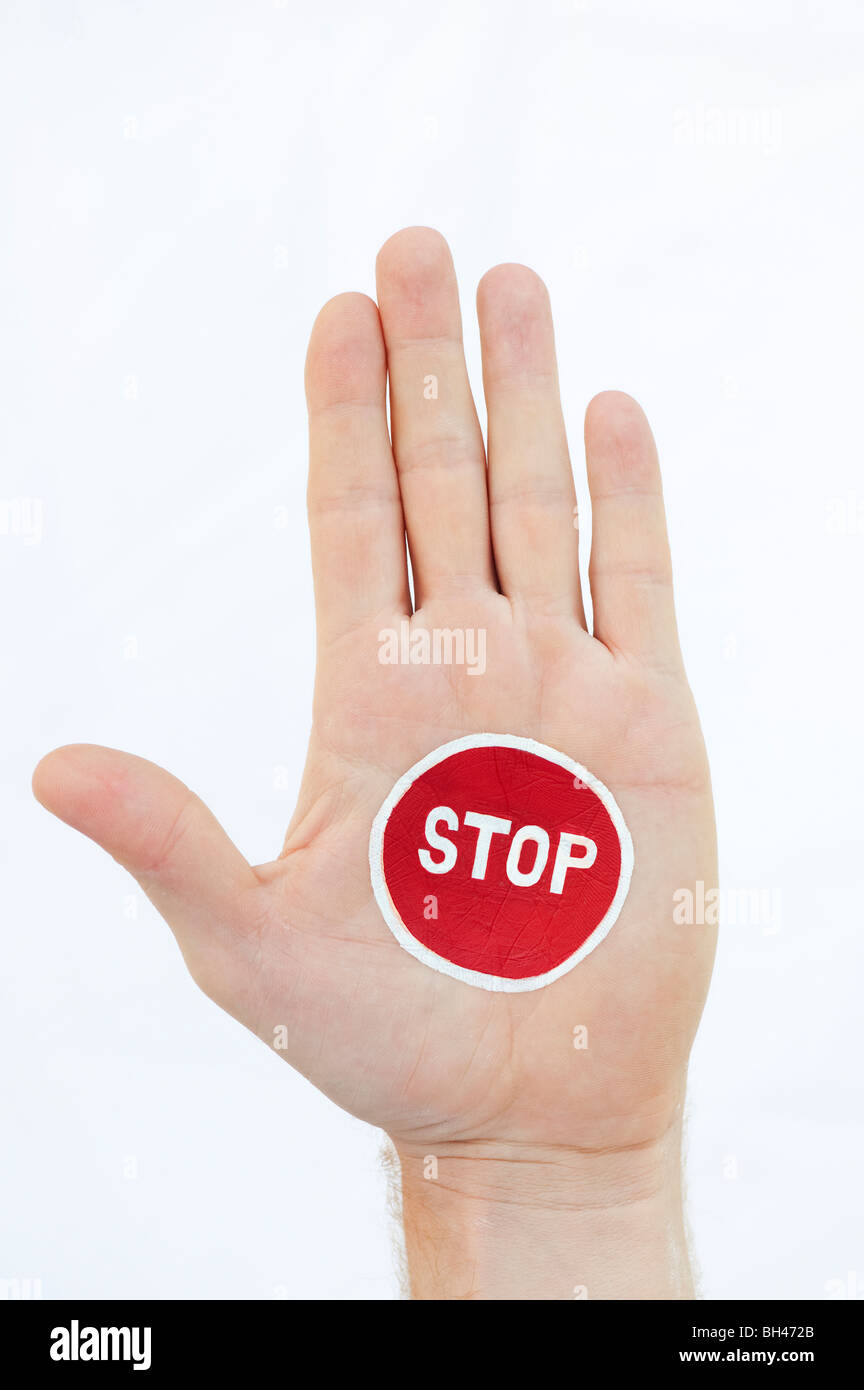 Painted STOP sign on hand against white background - Stock Image