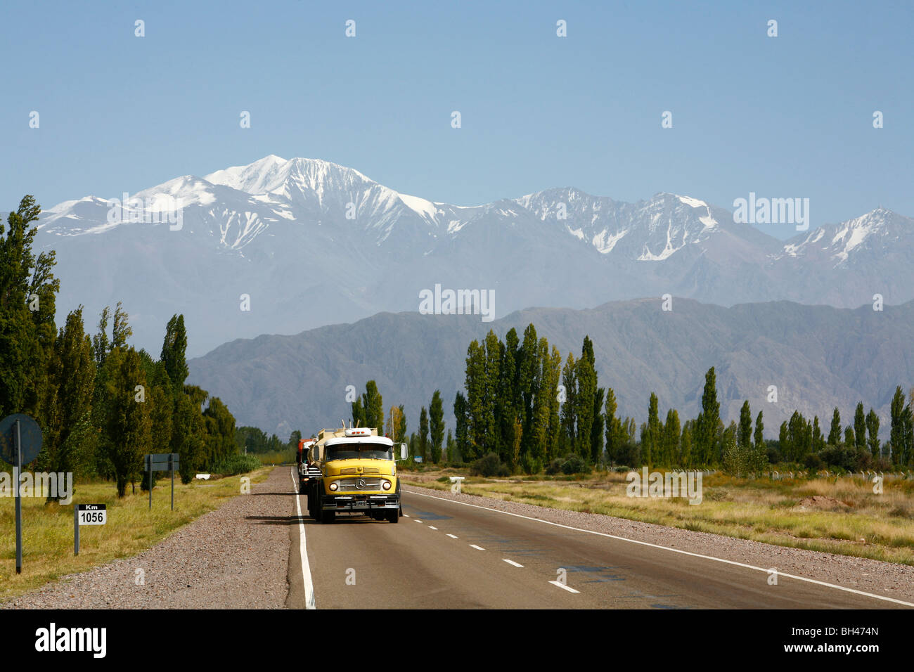 Truck on a road with the andes Mountains in the background, Mendoza, Argentina. - Stock Image