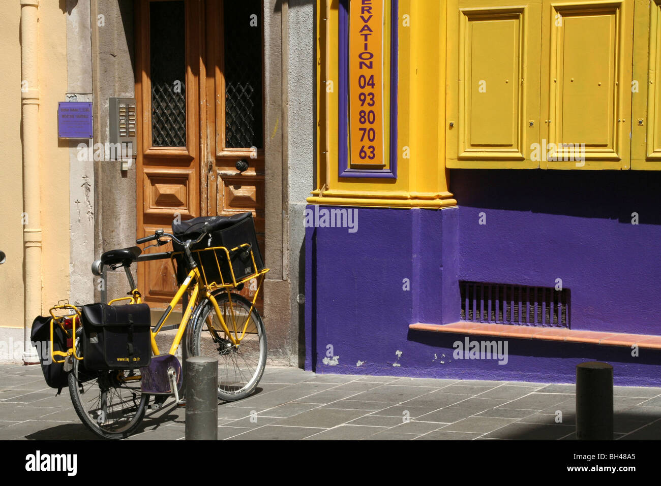 Street scene with a bicycle in front of a door and colourful frontage of a building. - Stock Image