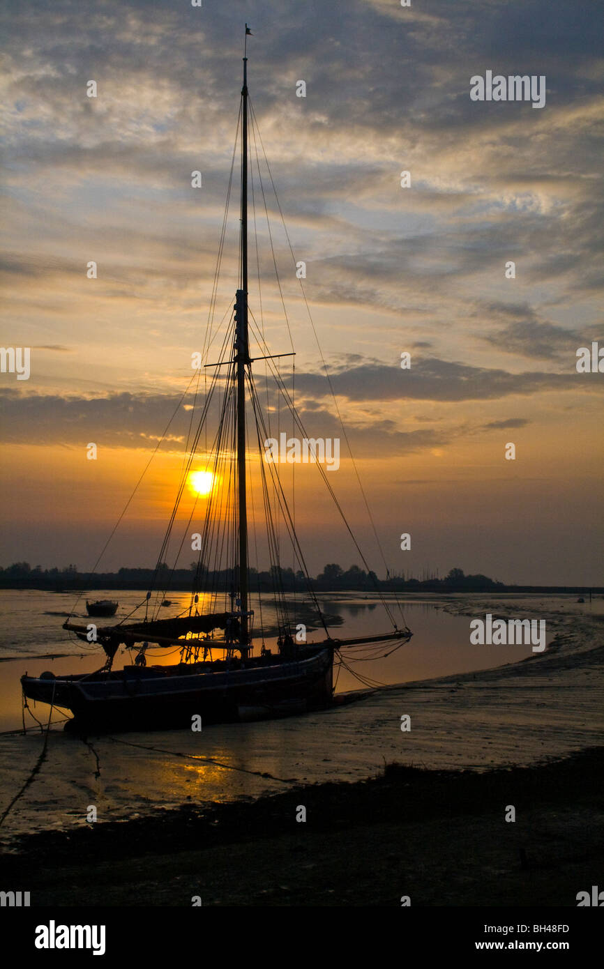 Oyster smack silhouetted against the early morning sun at Maldon. - Stock Image