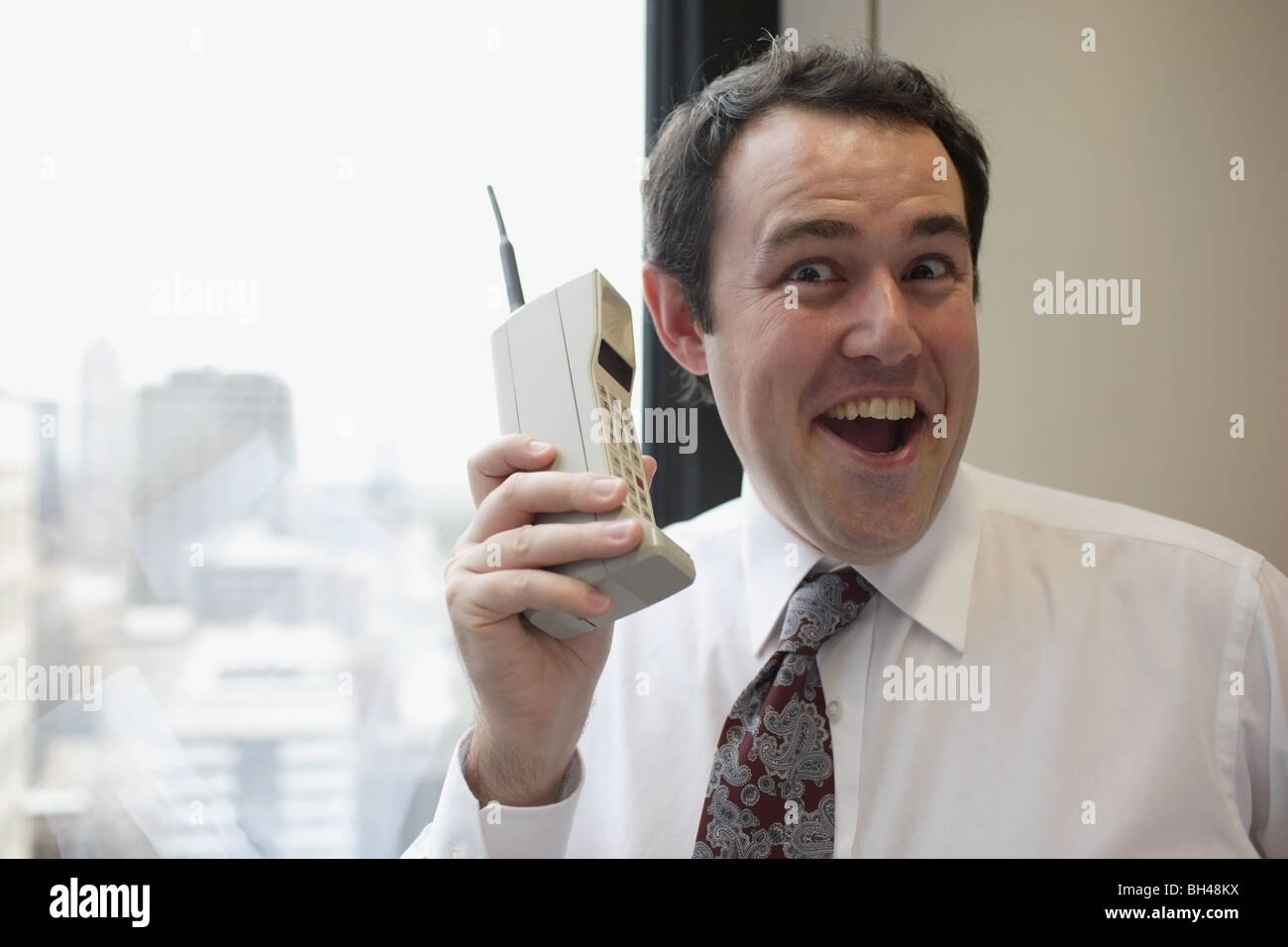 Businessman holding an old mobile telephone, laughing - Stock Image
