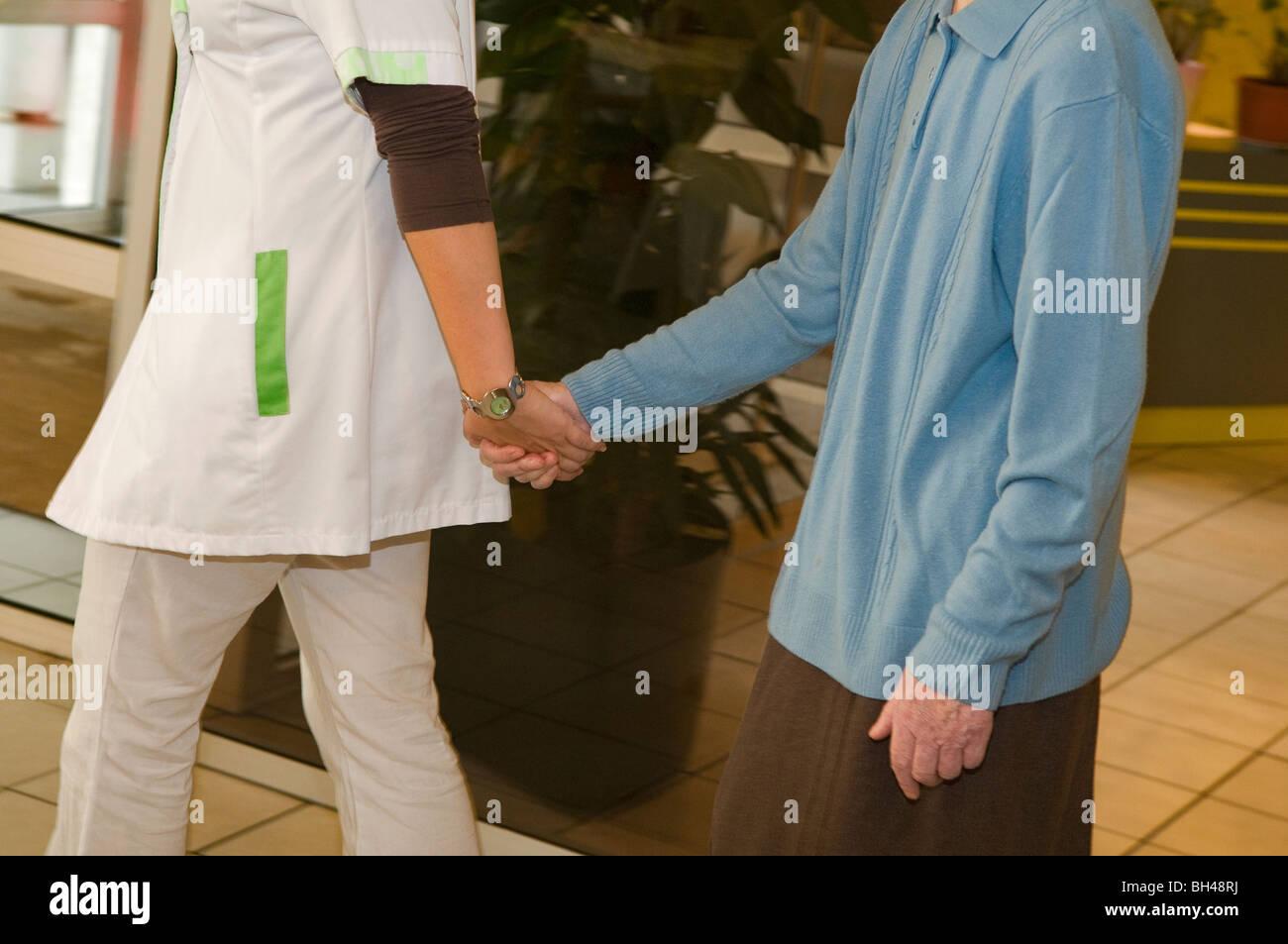 Carer handing an Alzheimer resident in nursing home - Stock Image