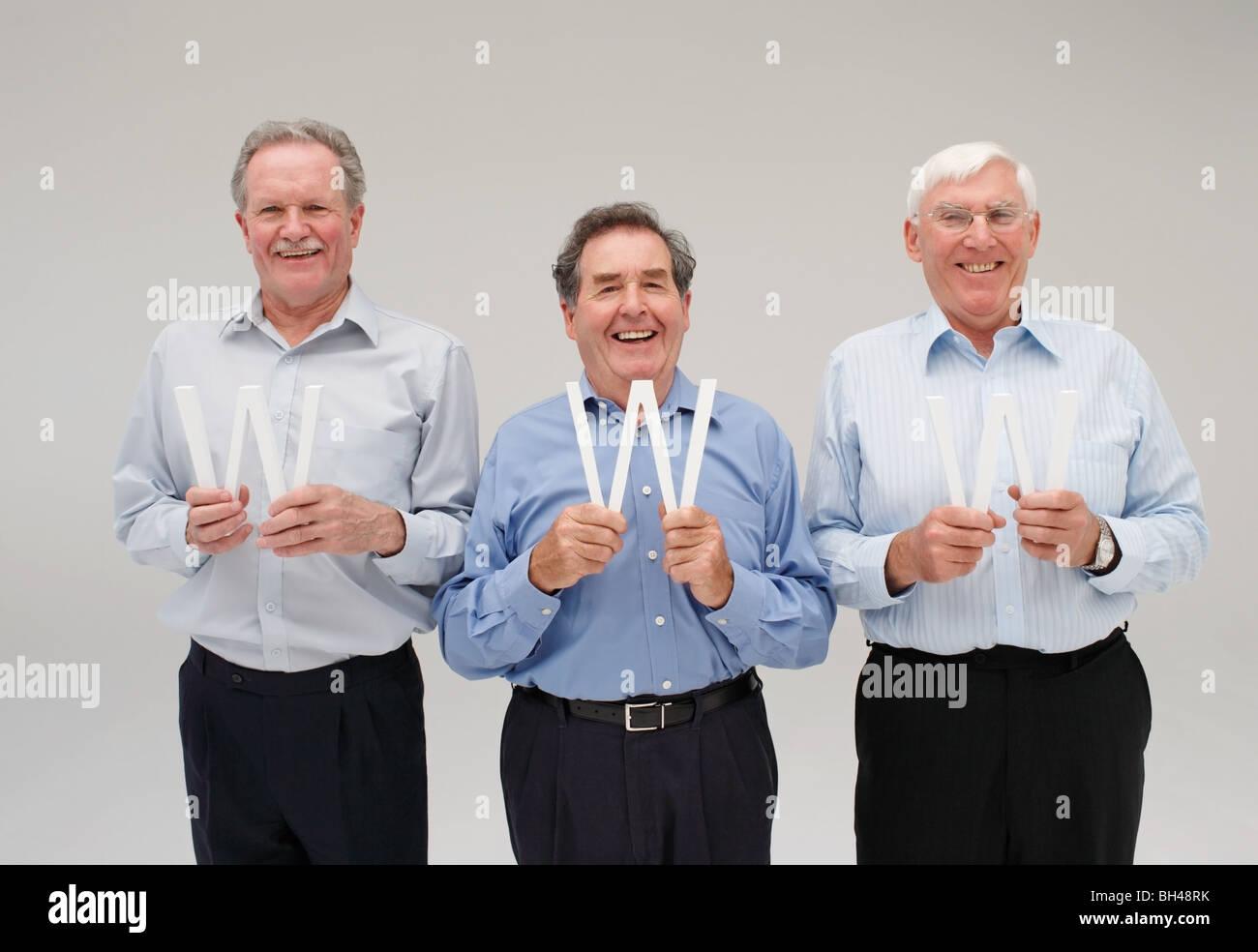 Three senior businessmen each holding the letter 'W', smiling - Stock Image