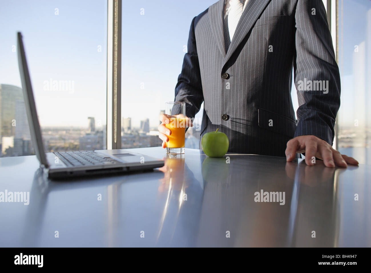 A businessman holding a glass of orange juice next to an apple and a laptop computer on an office desk Stock Photo