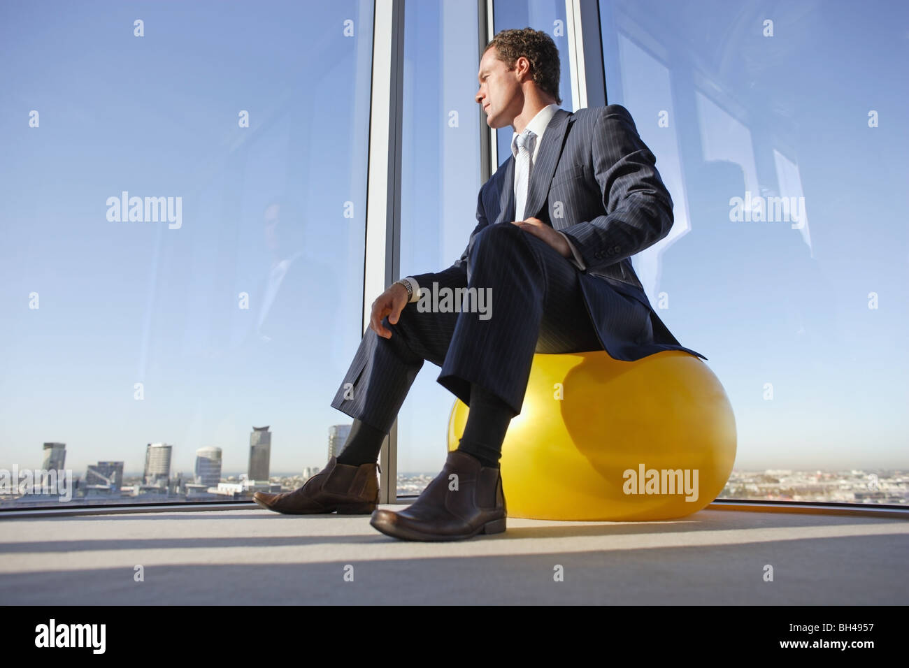 A businessman sitting on a swiss ball in the corner of an office looking out of the window across the skyscrapers Stock Photo