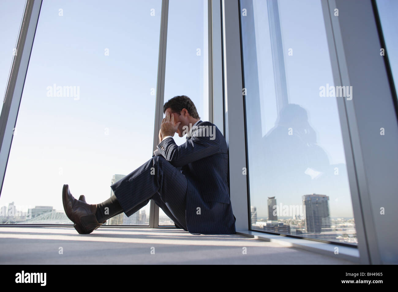 A businessman sitting on the floor in the corner of an office skyscraper with his head in his hands - Stock Image