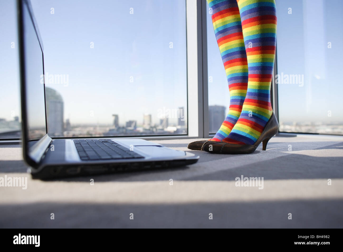 A woman's legs wearing multi colored striped stockings standing next to a laptop computer in an office - Stock Image