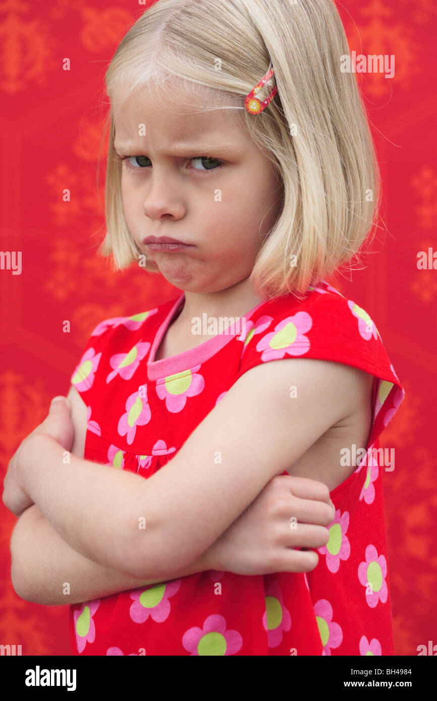 Young girl wearing a red dress standing with her arms folded frowning with a miserable expression against red wallpaper - Stock Image