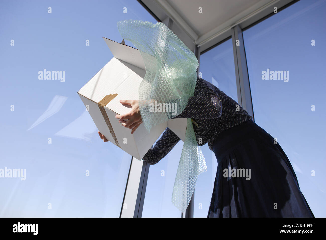 A woman's head buried deep inside a box full of bubble wrap in an office - Stock Image