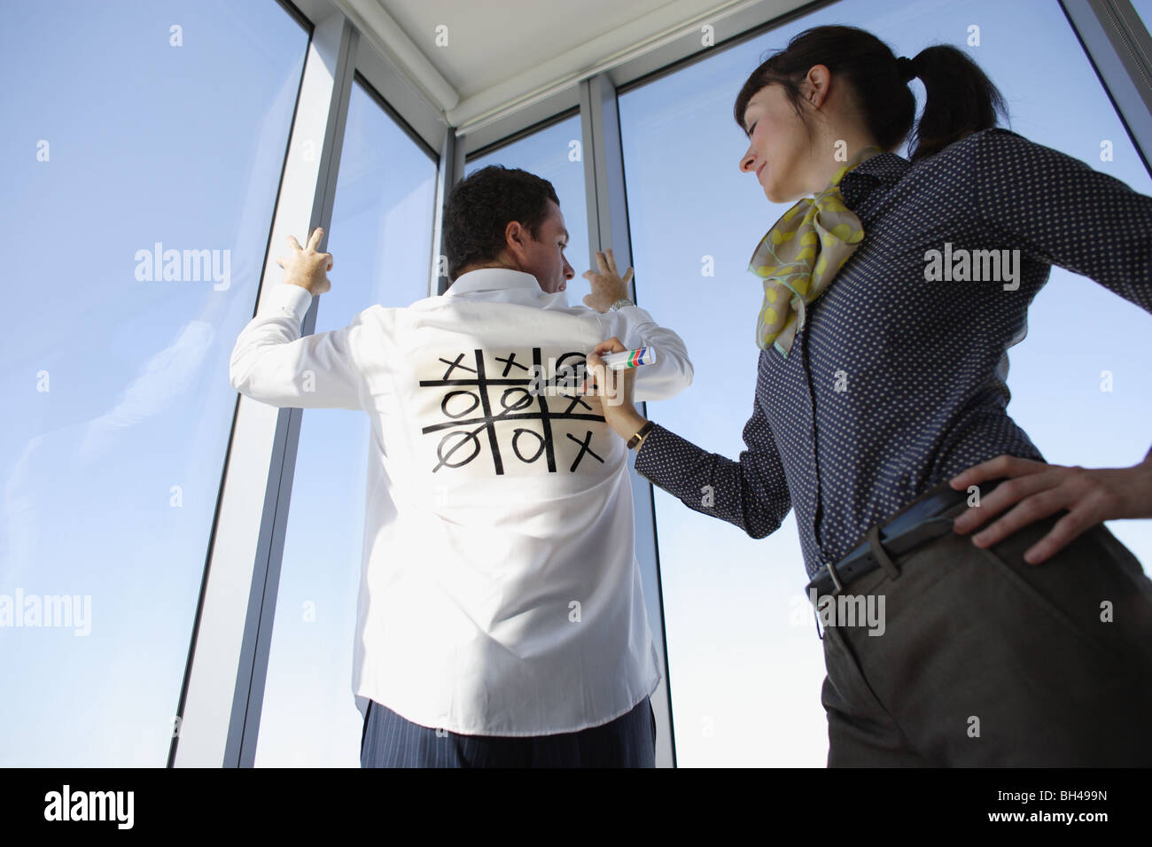 A woman playing Noughts and Crosses ( Tic Tac Toe ) on the back of a man's white business shirt - Stock Image