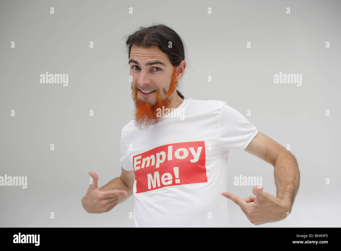 A young man pointing to his t-shirt with the message 'Employ Me!' printed over it, smiling - Stock Image