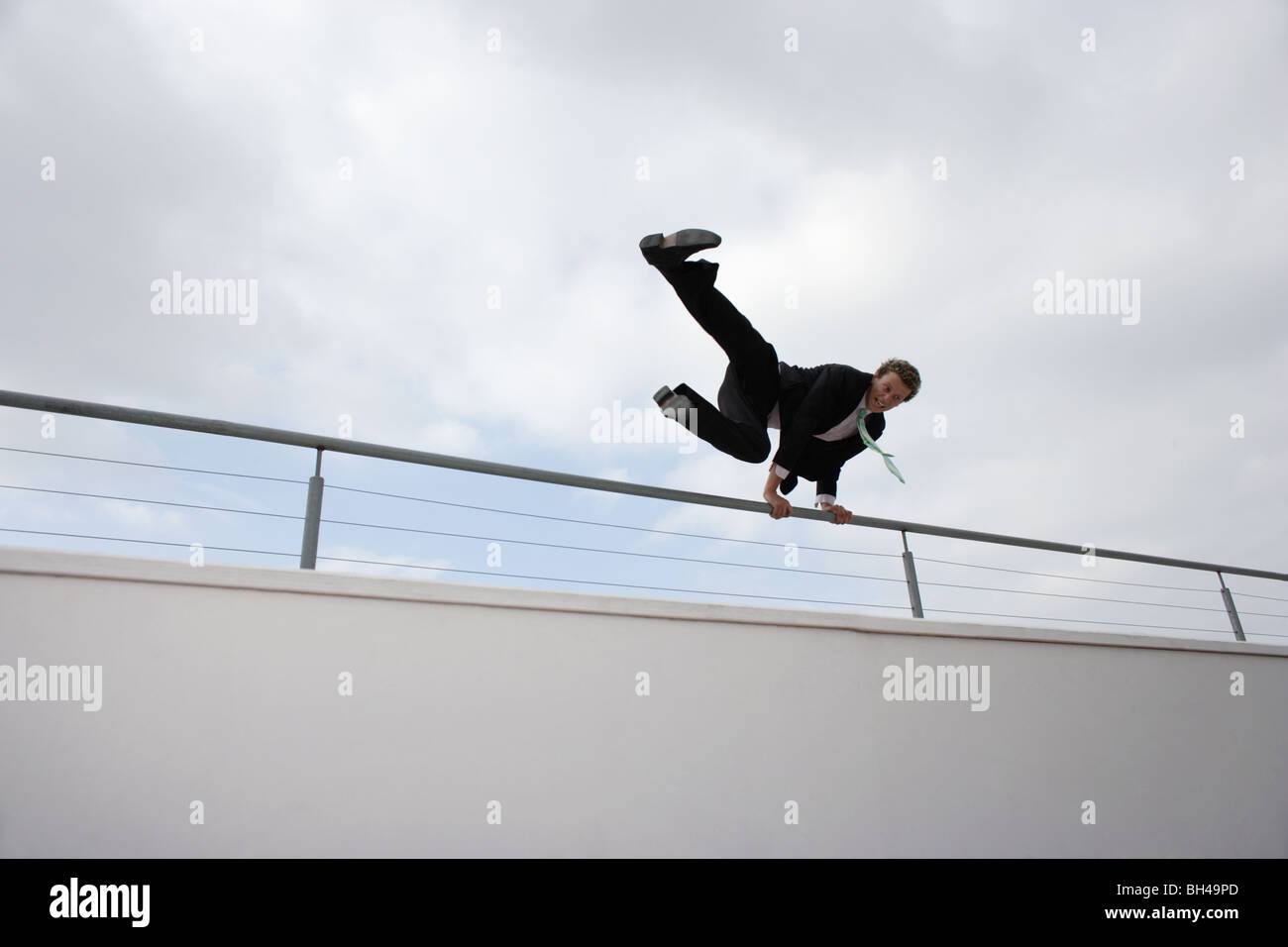 Young businessman leaping over a wall in the city - Stock Image