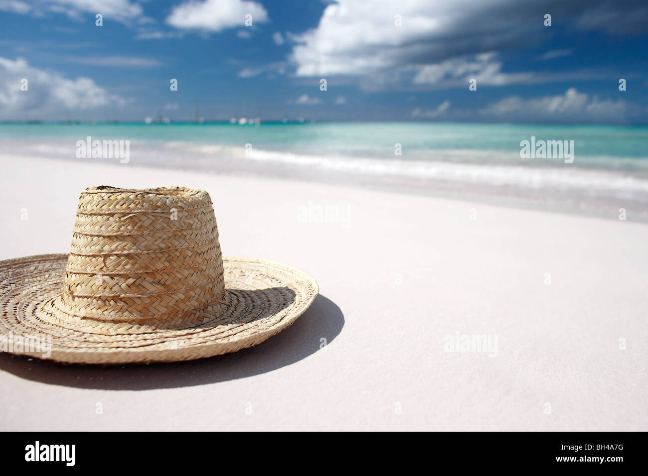 A straw sun hat lying on a white sandy tropical deserted beach - Stock Image