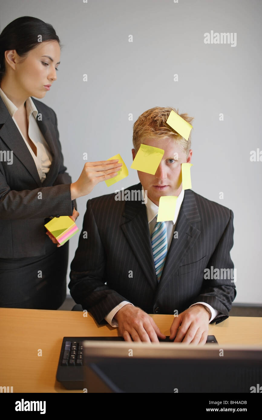 A businesswoman placing sticky notes of paper on to a businessman's face as he sits at a desk working on a computer - Stock Image